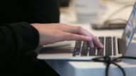 A male customer uses his personal laptop computer at a table in a coffee shop in London UK on Friday April 25 Close shot hands typing at an Apple Inc...