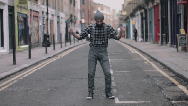 Male dancing in street looking to camera