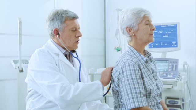 Male doctor auscultating the female patients lungs on her back