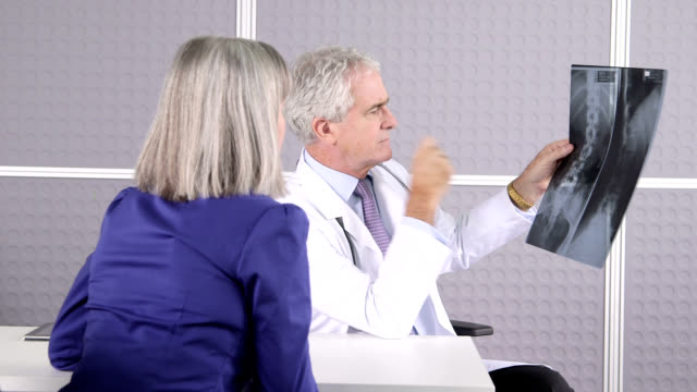 Male doctor discussing X-ray with patient