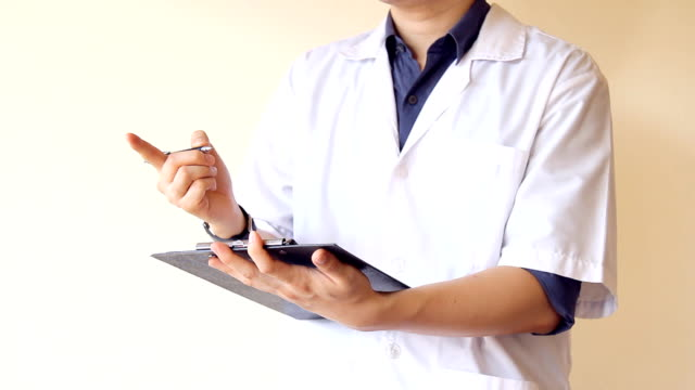 male doctor holding patient note on clipboard, writing and discussing about patients' symptoms