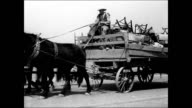 Male driving horse drawn wagon loaded w/ belongings furniture family Family loading up truck w/ sign 'California or Bust' Dust Bowl refugees man...