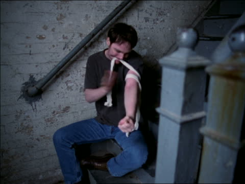 Male drug addict sitting in stairwell putting tourniquet on arm / taps veins + prepares needle