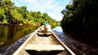 HD Male explorer sailing on indigenous canoe in the Amazon