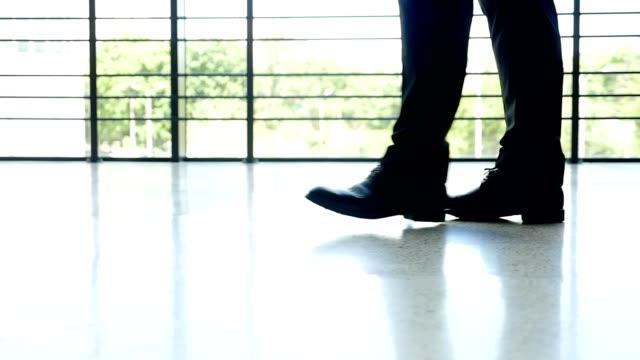 Männliche Füße eines Geschäftsmannes zu Fuß auf dem Boden des Amtes