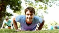 Mannelijke fitness instructeur glimlacht terwijl het doen van push ups tijdens de oefening buiten les