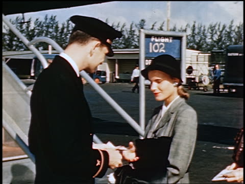 1950 male flight attendant/ticket agent taking tickets from two women boarding airliner outdoors