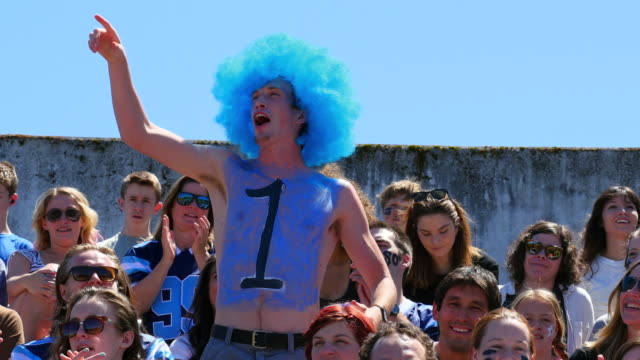 MS Male football fan wearing wig with a number one painted on chest standing in stadium cheering