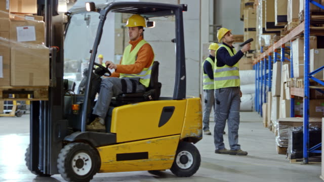 Male forklift operator driving in the warehouse with a pallet on the forks