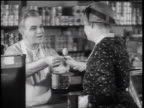 B/W 1933 male grocer giving canned peach slice to senior woman / woman trying peach + nodding