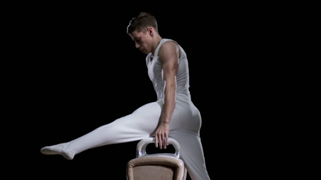 SLO MO Male gymnast mounting the pommel horse and performing his routine
