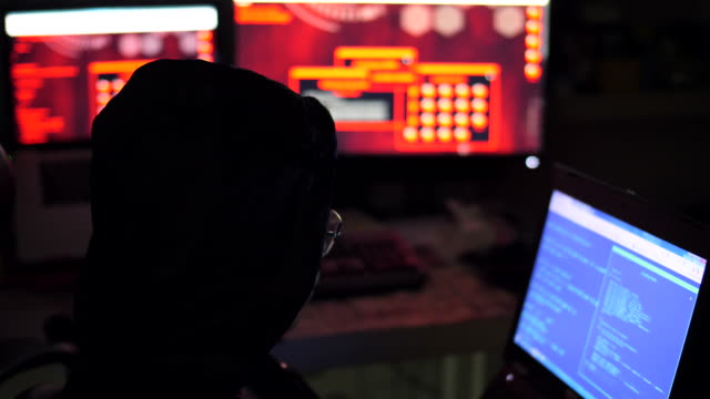 Male hacker works on a computer with data on screens