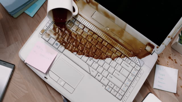 SLO MO LD Male hand accidentally knocking over a cup of coffee and spilling it on his laptop