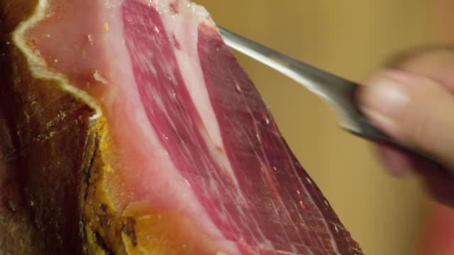 ECU male hand cutting thin slices off Pata Negra ham ('jamon')