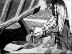 Male hand placing hammer in wagon hitch hole LA SOFT FOCUS LS Woman in long dress apron carrying basket up steps of porch trunk open in yard wooden...