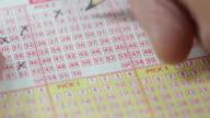 Maschile mani usando una matita per contrassegnare i numeri della lotteria