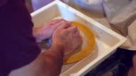 Mannelijke handen vormen een bal uit klei