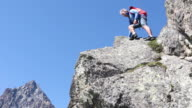 Male hiker ascends onto ridge crest, mountains behind