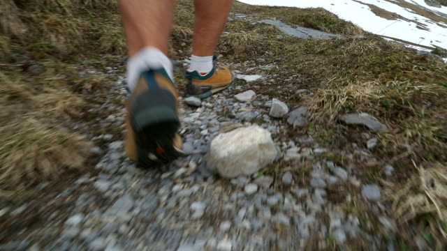 Male hiker ascends rugged spring mountain path towards mountain face