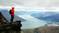 Male hiker climbs to mountain summit above lake