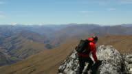 Male hiker climbs to mountain summit above mountain range