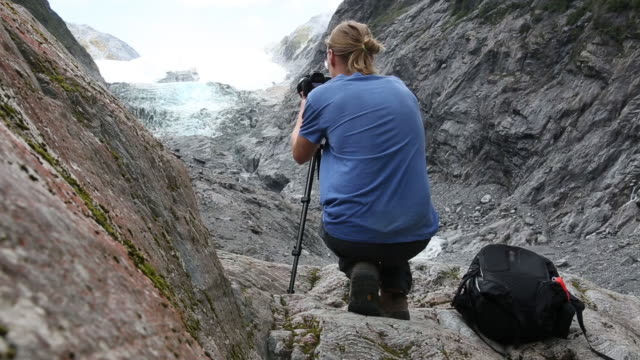 Male hiker composes picture of glacier from viewpoint