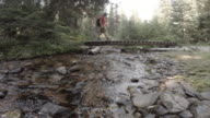Male hiker crosses small wooden bridge over river