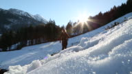 Male hiker jumps onto icy path coming from a distant mountain