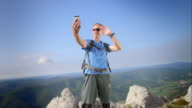 Male hiker on a video call on mountain top