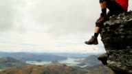 Male hiker relaxes on mountain promontory above lakes