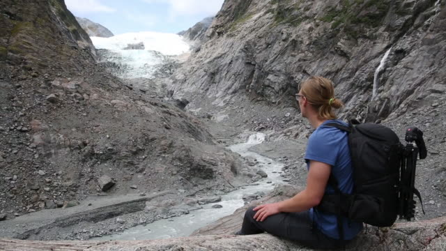 Male hiker rests on glacial slabs and looks toward glacier