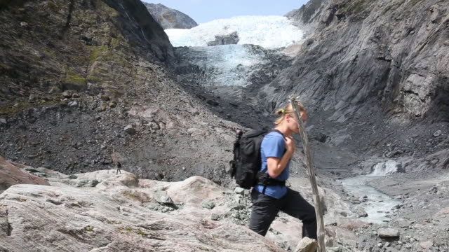Male hiker walks through glacial slabs and looks toward glacier