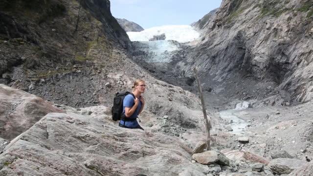 Male hiker walks through glacial slabs and looks toward glacier