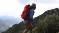 Male hiker walks through meadow above mountains