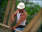 CANTED male Hispanic construction worker sawing board + throwing hard hat into air / runs offscreen