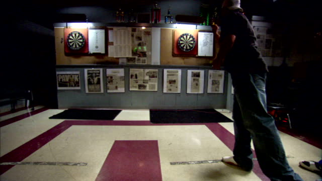 Male in backward cap tee shirt throwing darts at board on pub wall w/ boxing clippings displayed trophies above lighted boards Tavern games social...