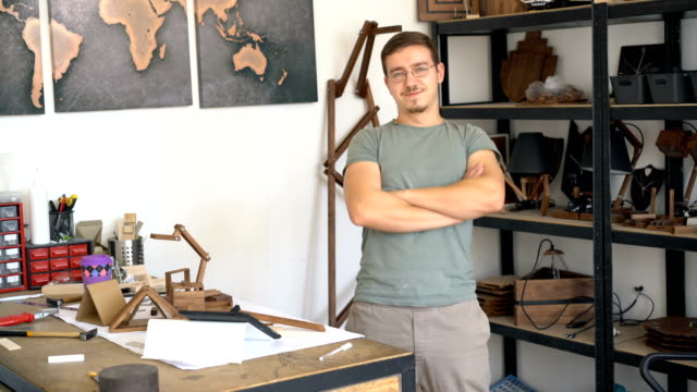 Male in his design studio, looking and smiling at camera.