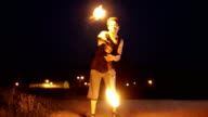 Male is dancing with fire outdoors