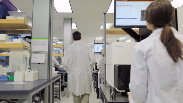 MS POPV Male Lab technician carrying samples through lab / Vancouver, BC, Canada
