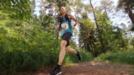 SLO MO CS Male marathon competitor running on a forest trail