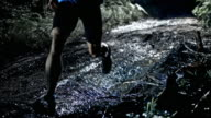 SLO MO DS Male marathon competitor running on a muddy trail at night