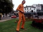 A male model wears an orange catsuit