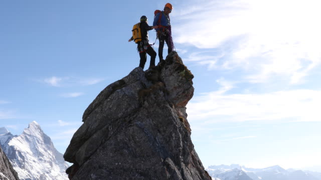 Male mountaineers climb rock pinnacle, mountains below
