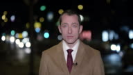 Male news reporter reporting live to the studio from the city at night