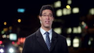 Male news reporter reporting live to the studio from the city center at night