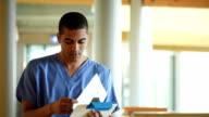 male nurse checking notes in a hospital corridor