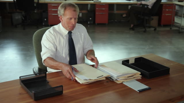 MS Male office worker with stack of paperwork on desk / Portland, Oregon, USA