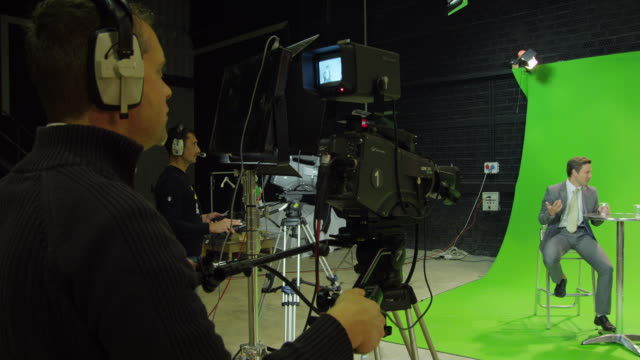 WS PAN male presenter and female guest sitting on stools in front of green screen in TV studio, chatting, camera crew  in foreground