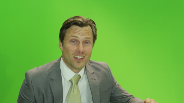 CU male presenter in front of green screen in TV studio, talking,  looking to camera