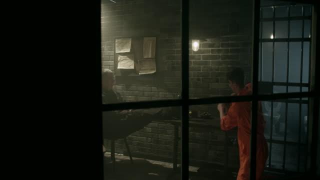 Male prisoner cleaning table in jail thru window